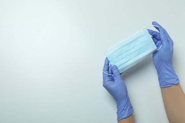 Mãos em luvas médicas segurando máscara em fundo branco isolado