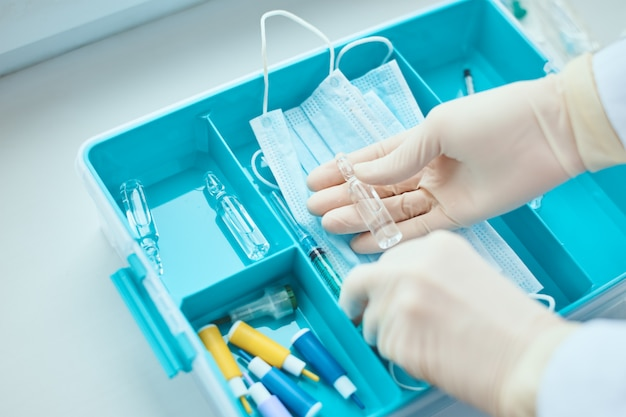 Mãos em luvas médicas tomando seringa da caixa do medicamento