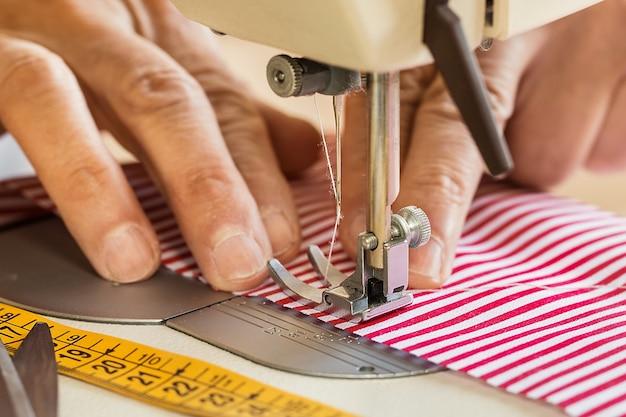 Mãos, em, máquina de costura, segurando, algum, tecido