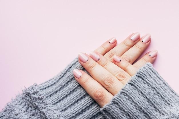 Mãos em suéter de malha com unhas nude rosa com pontos pretos em rosa