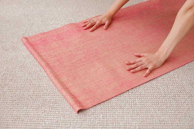 Mãos em um tapete de ioga. ioga no estúdio