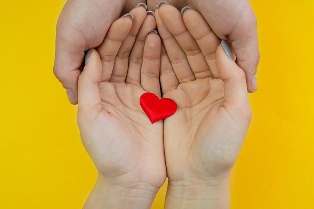 Mãos em uma superfície amarela com coração