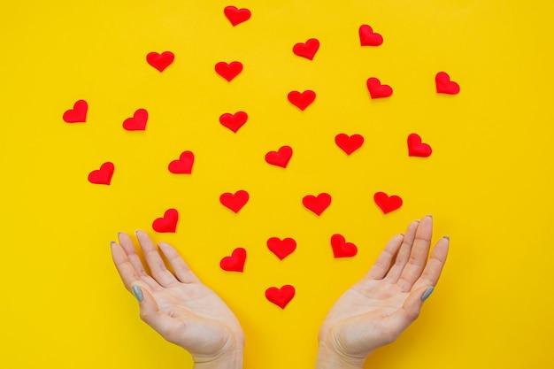Mãos em uma superfície amarela com corações