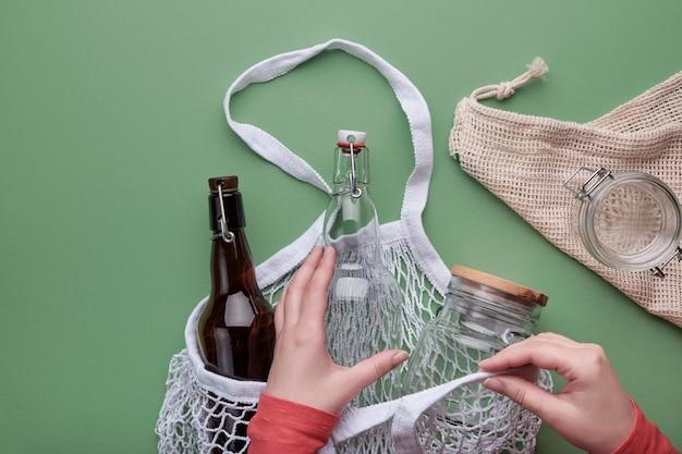 Mãos, embalagem de garrafas de vidro e jarra em saco de malha