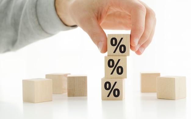Mãos empilhando sinais de porcentagem em um bloco de brinquedo de madeira Foto Premium