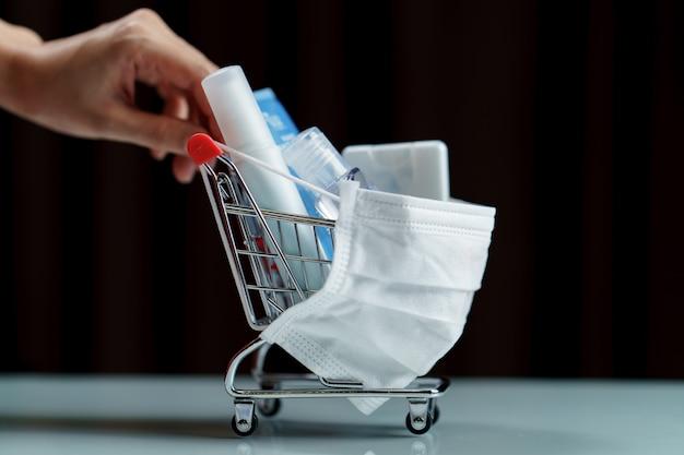 Mãos empurrando produtos de carrinho e desinfetantes com máscara protetora contra vírus corona ou proteção covid-19.