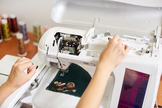 Mãos enchendo o fio na máquina de costura