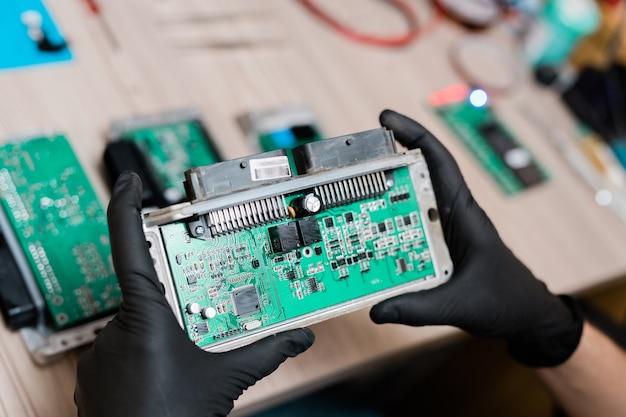 Mãos enluvadas do mestre de serviço de reparos segurando parte do dispositivo desmontado enquanto o examina e tenta descobrir a causa da quebra