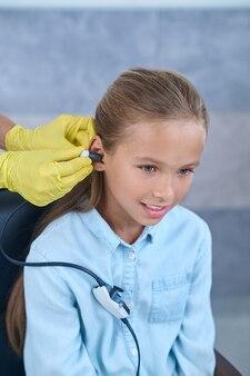 Mãos enluvadas fazendo teste de audição para menina