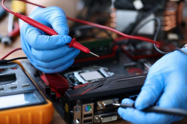 Mãos enluvadas, na mesa, reparar um dispositivo eletrônico