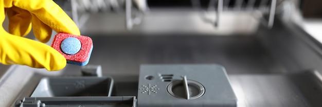 Mãos enluvadas segurando a máquina de lavar louça tablet de lavagem
