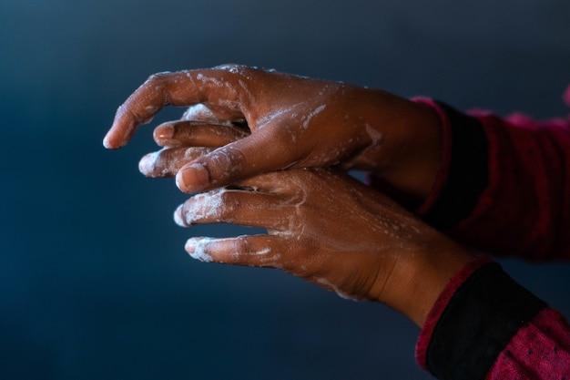 Mãos ensaboadas de uma pessoa - importância de lavar as mãos