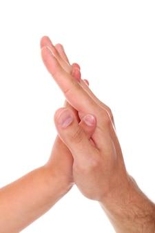 Mãos entrelaçadas de criança e adulto.