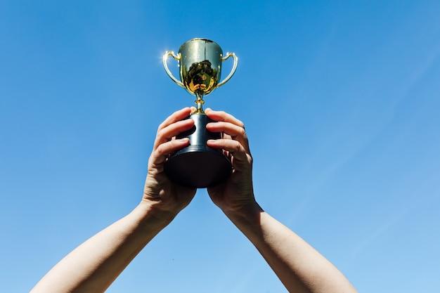 Mãos erguem a taça de um campeão, com o céu ao fundo. conceito de vitória