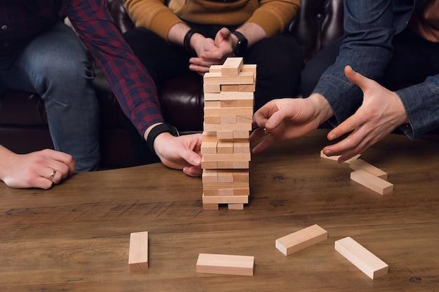 Mãos erguem uma torre de varas de madeira, conceito de trabalho em equipe, jogo de equipe. foto de alta qualidade