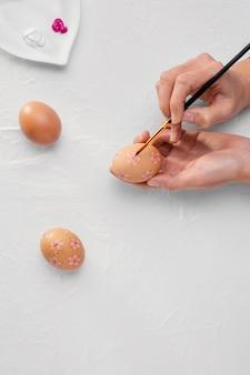 Mãos erguidas com pincel pintando ovos de páscoa