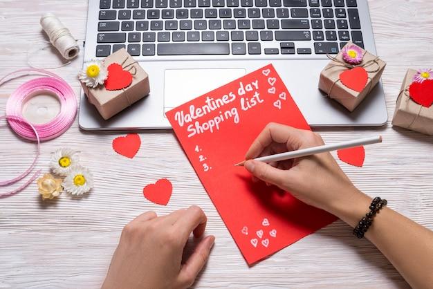 Mãos, escrevendo a lista de compras do dia dos namorados na mesa de madeira