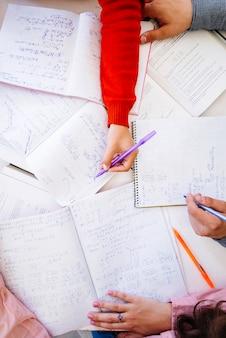Mãos escrevendo cálculos na área de trabalho com notebooks