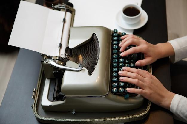 Mãos escrevendo na velha máquina de escrever perto da xícara branca