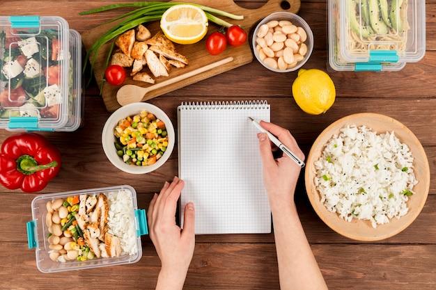 Mãos, escrevendo no caderno com comida de anúncio de caçarolas