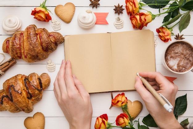 Mãos escrevendo no caderno em branco, mesa com saborosos croissants e confeitaria pronta para comemorar