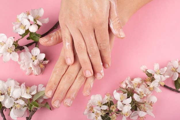 Mãos espalhando creme close-up sobre um fundo rosa com galhos de flores brancas. hidratação da pele, cuidados com as mãos, beleza, cosméticos, prevenção de rugas, envelhecimento da pele