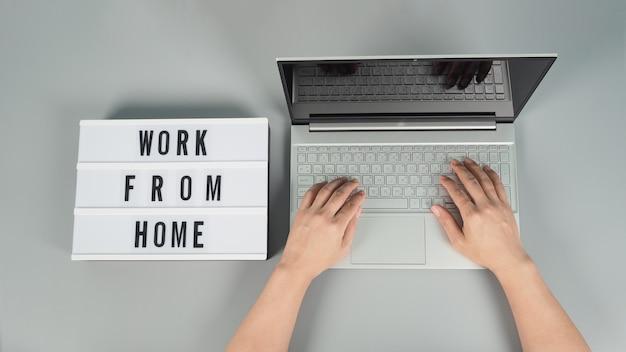Mãos está digitando no computador, laptop ou notebook em fundo cinza. studio shot.top eye view. caixa de luz no trabalho da palavra casa.