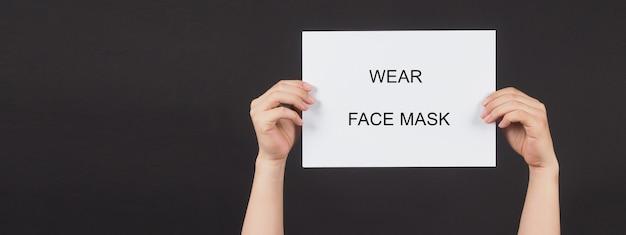 Mãos está segurando uma máscara de rosto do desgaste da palavra da escrita da placa de papel em fundo preto.