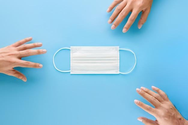 Mãos estendendo a mão para obter máscara facial médica para proteger de germes e vírus durante uma situação de pandemia