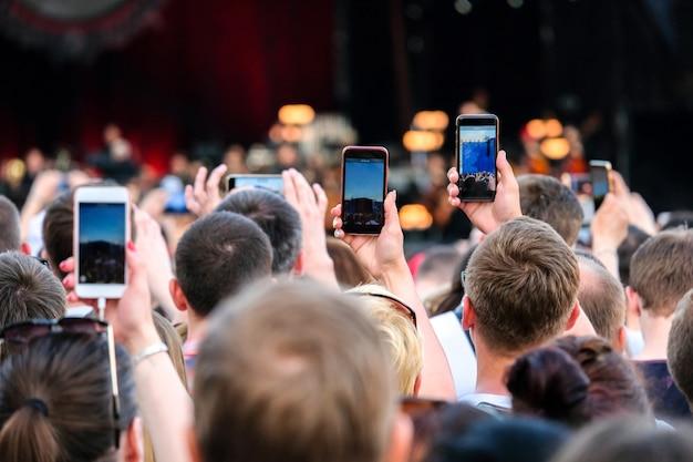 Mãos estendidas levantadas com os smartphones que fotografam a fase na multidão durante um concerto.