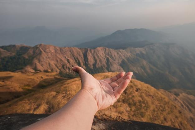 Mãos estendidas para receber luz natural e vista para a montanha, bela névoa da manhã. estilo hippie.