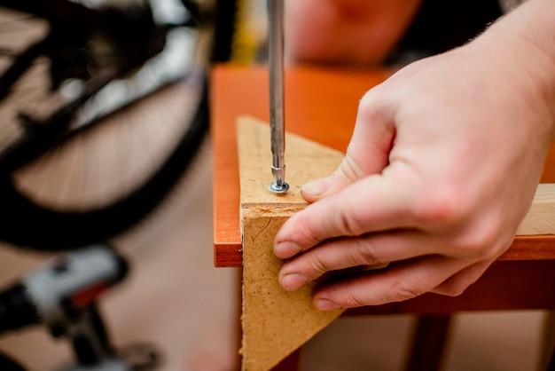 Mãos europeias brancas do homem com a chave de fenda que trabalha com madeira e parafusos. horizontal.