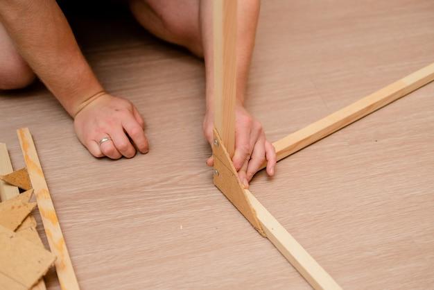Mãos europeias brancas do homem com a chave de fenda que trabalha com madeira e parafusos.