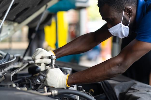 Mãos expertise mecânico de automóveis em serviço de reparo de automóveis. manutenção do carro e conceito de garagem de serviço automático. homem negro usando máscara médica protec virus corona