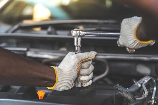 Mãos expertise mecânico de automóveis em serviço de reparo de automóveis. manutenção do carro e conceito de garagem de serviço automático.