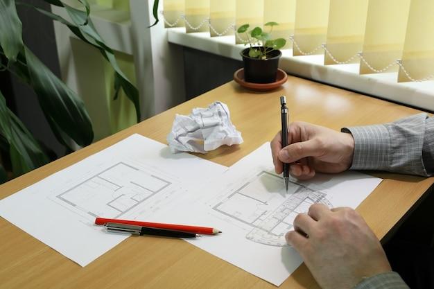 Mãos fazem anotações e medidas na planta arquitetônica