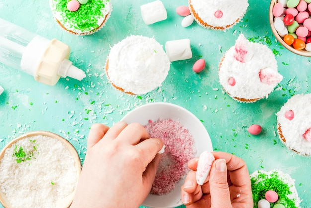 Mãos fazendo cupcakes de páscoa com orelhas de coelho