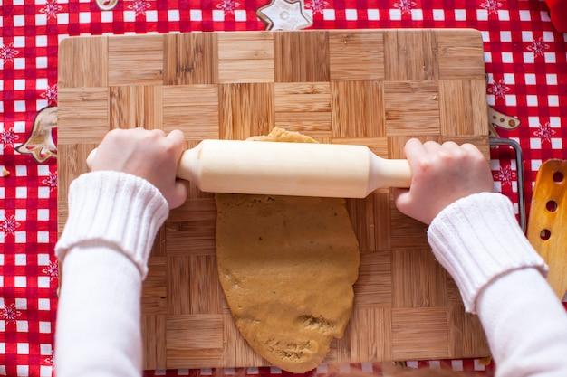 Mãos fazendo de massa natal homem-biscoito