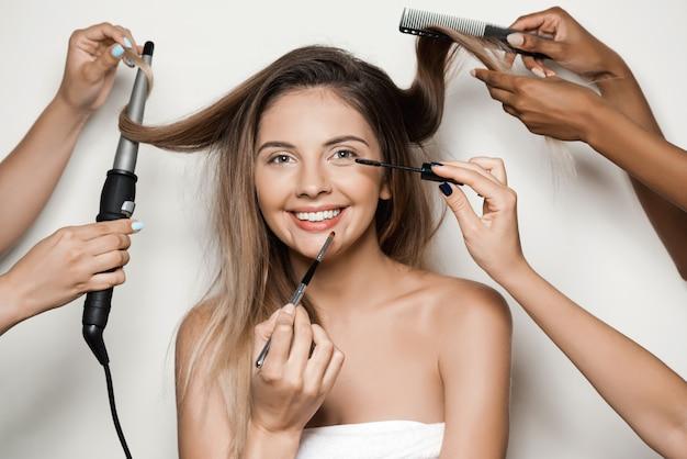 Mãos fazendo maquiagem e penteado de mulher jovem e bonita