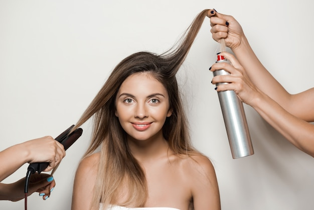 Mãos fazendo penteado para jovem mulher bonita