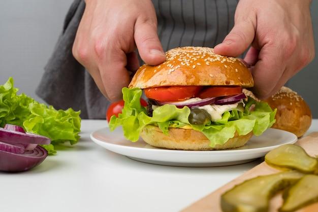 Mãos fazendo um hambúrguer saboroso