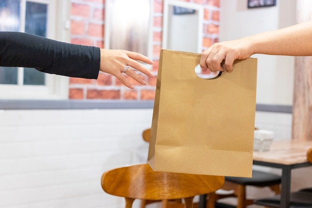 Mãos fazendo uma entrega de fast food