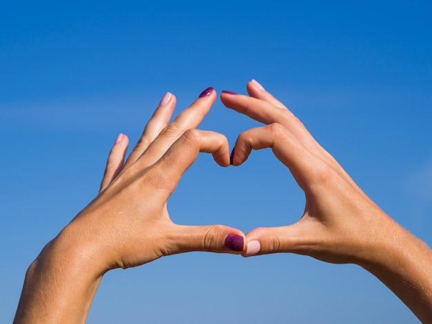 Mãos fazendo uma forma de coração no céu