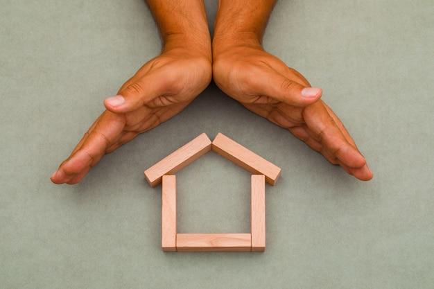 Mãos fechando casa de madeira.