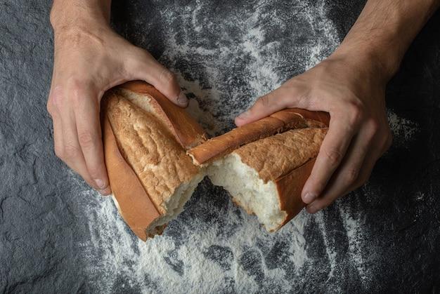 Mãos female partindo pão fresco, vista de cima.
