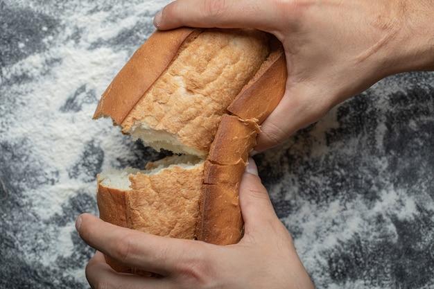 Mãos female quebrando pão fresco, vista superior do close up.
