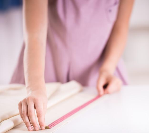 Mãos fêmeas no trabalho com fita de medição, close-up.