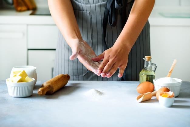 Mãos fêmeas que amassam a massa, cozendo o fundo. cozinhar ingredientes