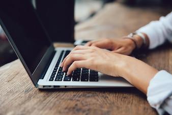Mãos fêmeas que datilografam no teclado do netbook, opinião do close-up. Conceito de negócios.