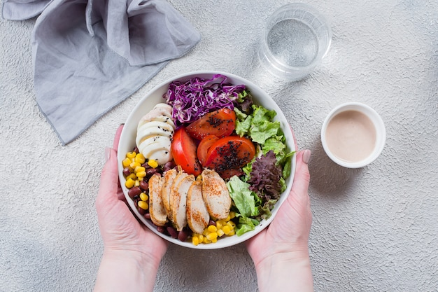 Mãos fêmeas que guardam a galinha, o ovo, os vegetais e o molho de assado da bacia do almoço.